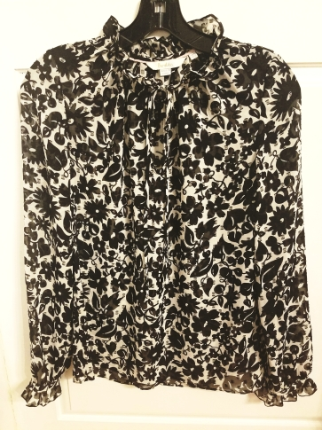 Sheer, floral, black and white blouse with ruflles. It has a self-tie neckline. By Boden.