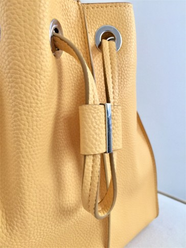 Closure detail of the ZARA yellow bucket bag
